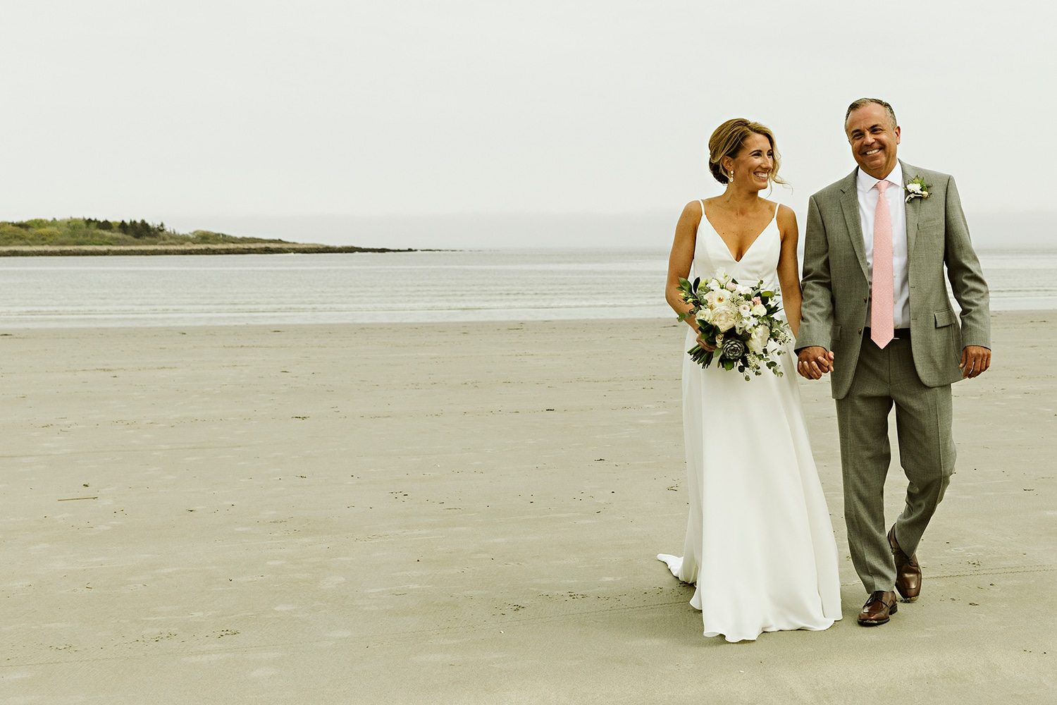 Bride and groom laughing on beach