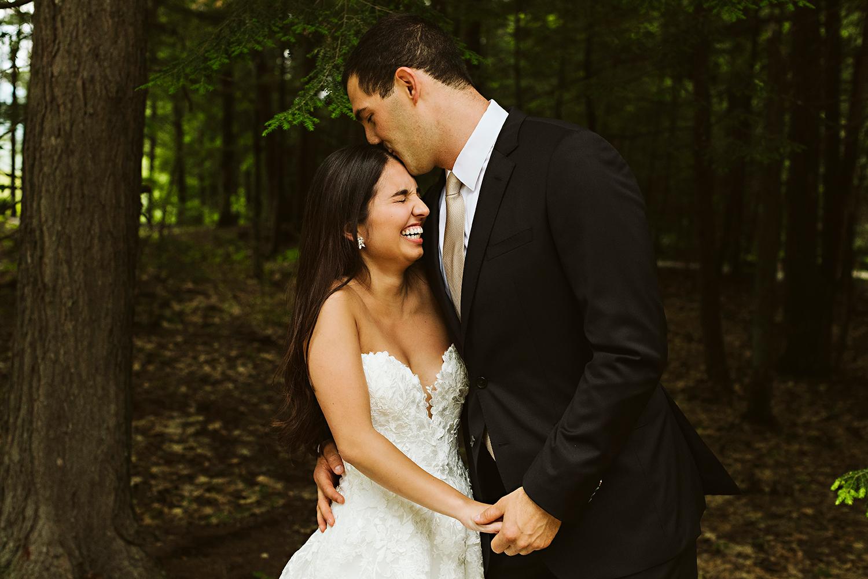 Bride laughing while groom kisses her head at Granite Ridge Estate & Barn Maine wedding