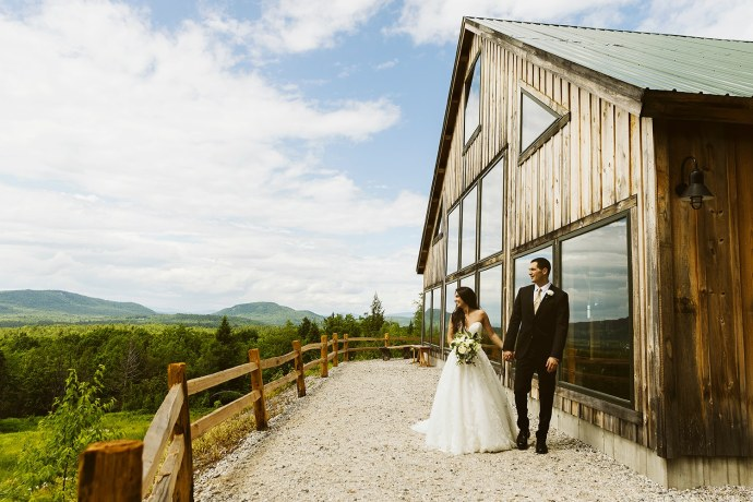 Bride and groom walk in front of Granite Ridge Estate & Barn
