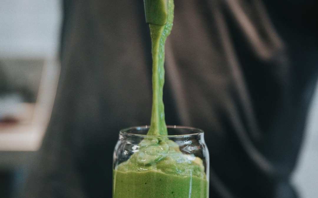 a green kale smoothie being poured into a glass