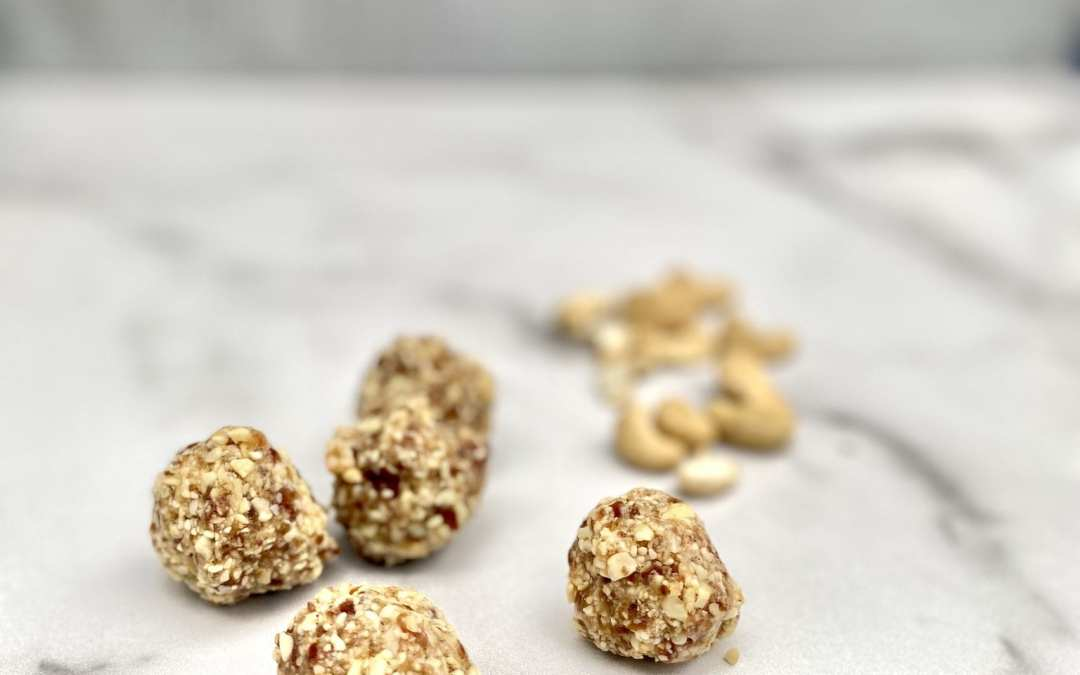 Cashew cookie balls on white marble counter top