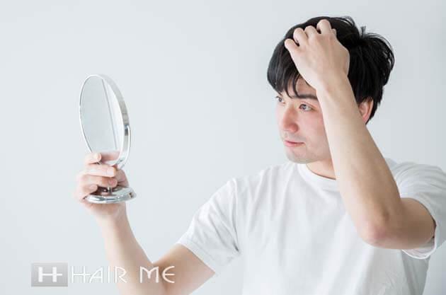 髪と手鏡で見る男性
