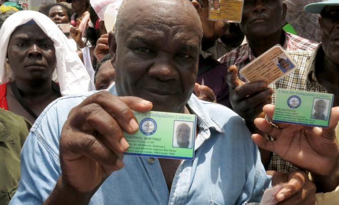 Un Haïtien montrant la carte qui prouve quil travaille dans une exploitation de canne à sucre depuis 1963