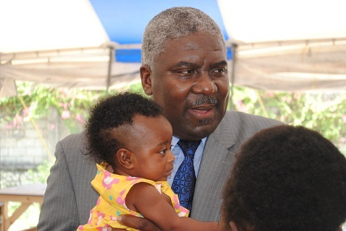 Christian Emmanuel Sanon with a child