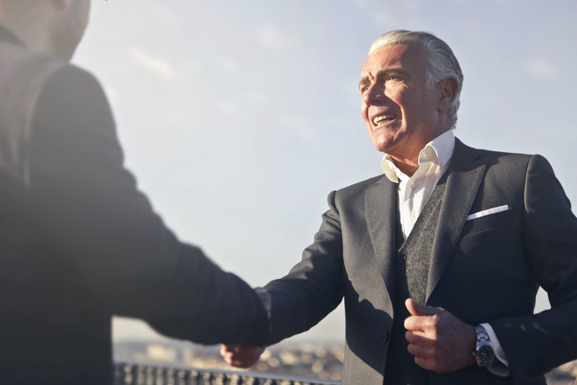 man in black suit shaking hands with another man