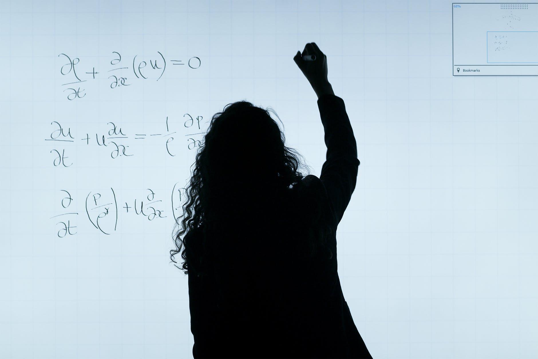woman writing on a whiteboard