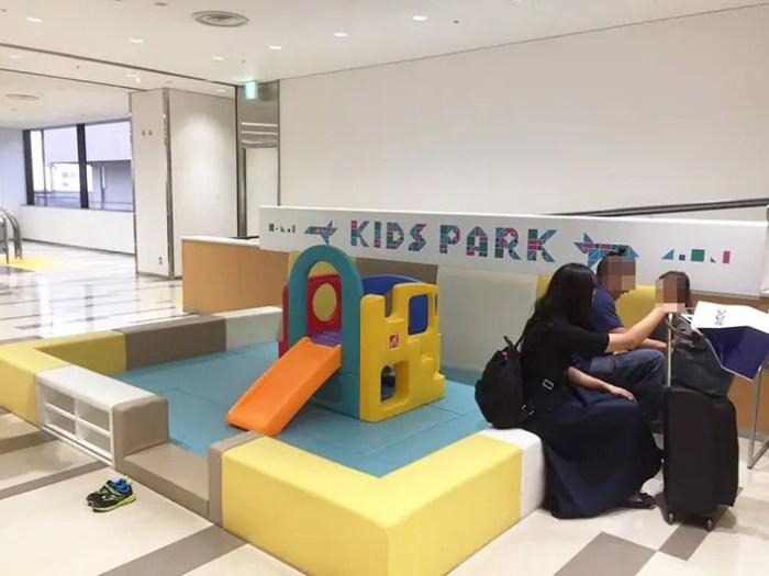 空港のキッズパークで遊ぶ親子