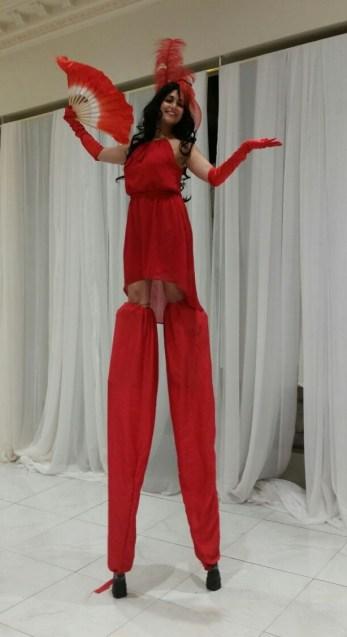 Hala on stilts stunning in red stiltwalker GTA Toronto