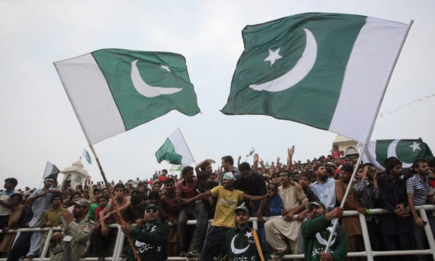 Men wave Pakistan's national flags as they attend a ceremony to mark the country's Independence Day at the Wagah border crossing with India on the outskirts of Lahore