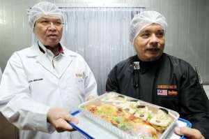 Ibrahim (left) and assistant executive chef Zainuddin Md Isa showing off some of Brahim's food products during a tour of the company's facilities. S.S.KANESAN/THE STAR