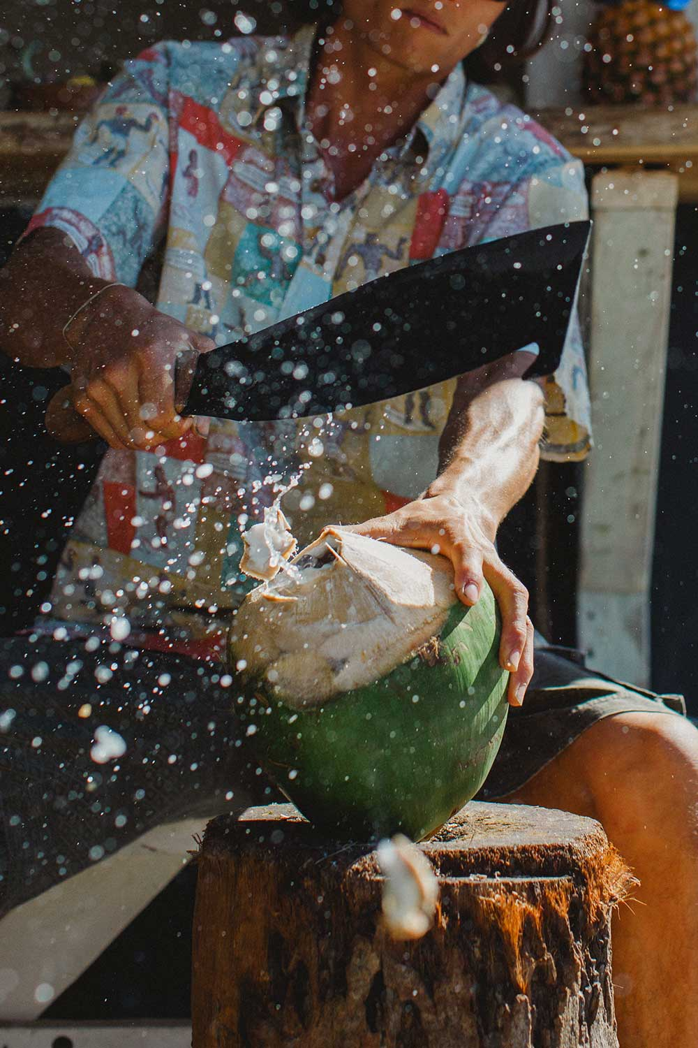 man chopping top of coconut and juice flying in air