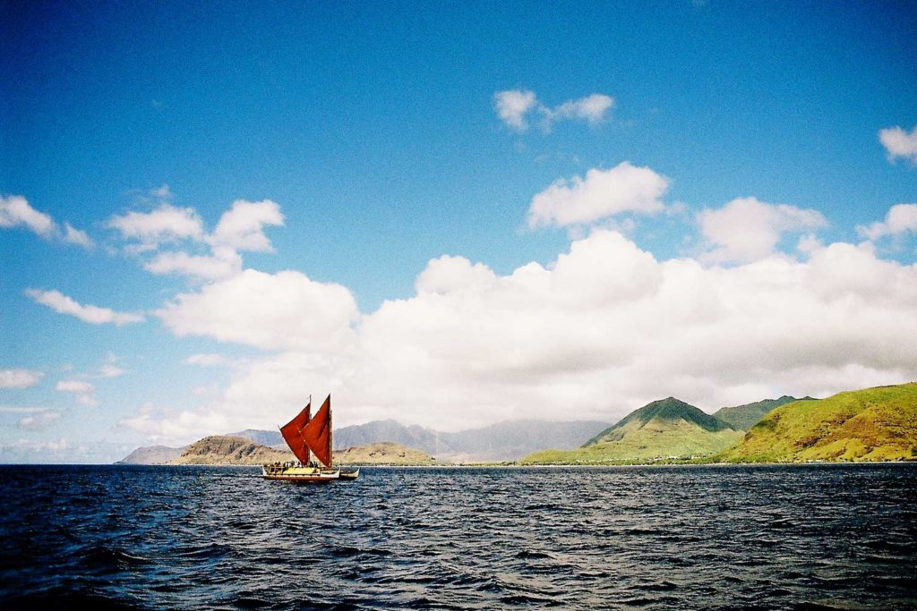 distant view of the Hōkūle'a's red sails