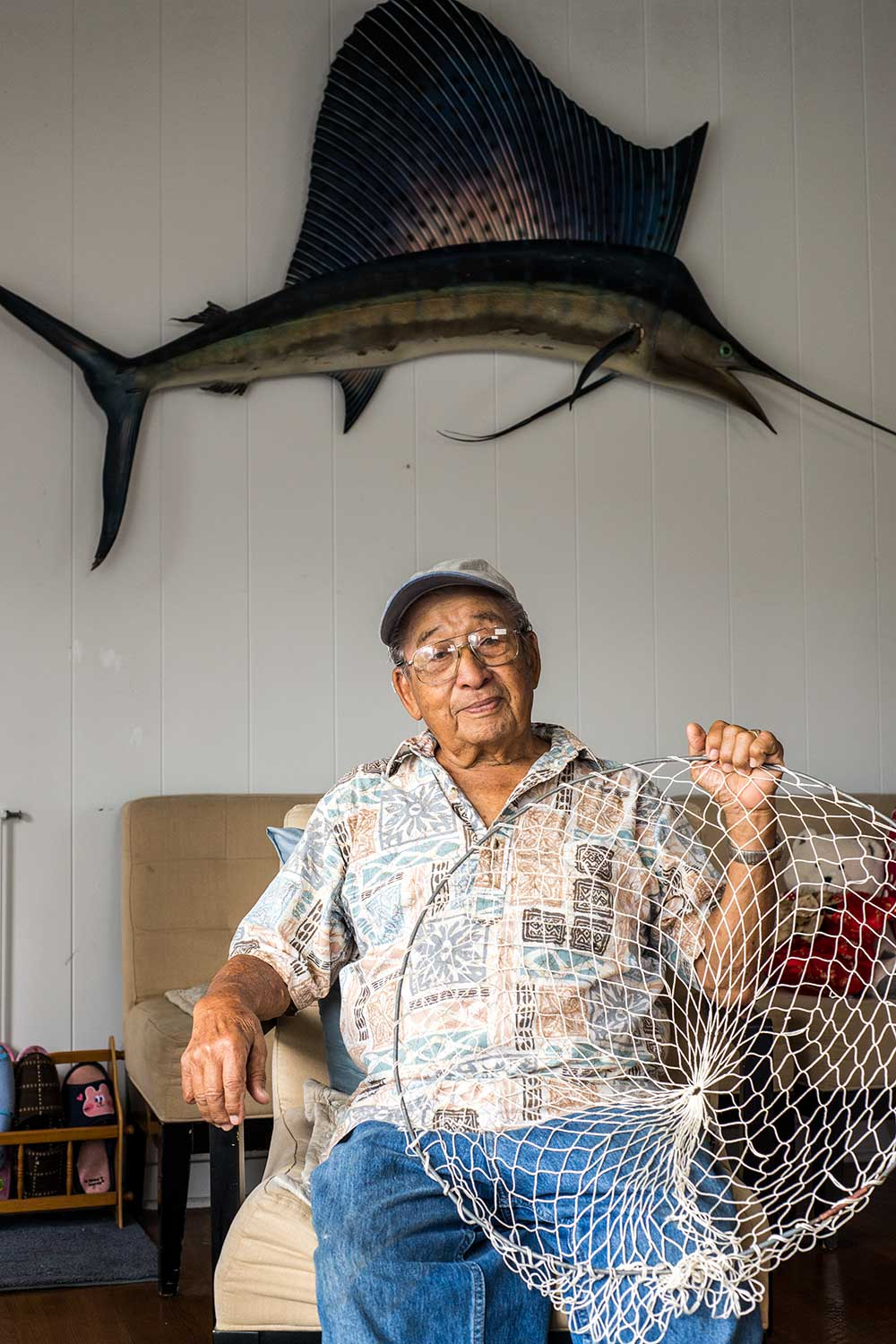 John Yu holding his handmade fishing net with swordfish hanging on wall above him
