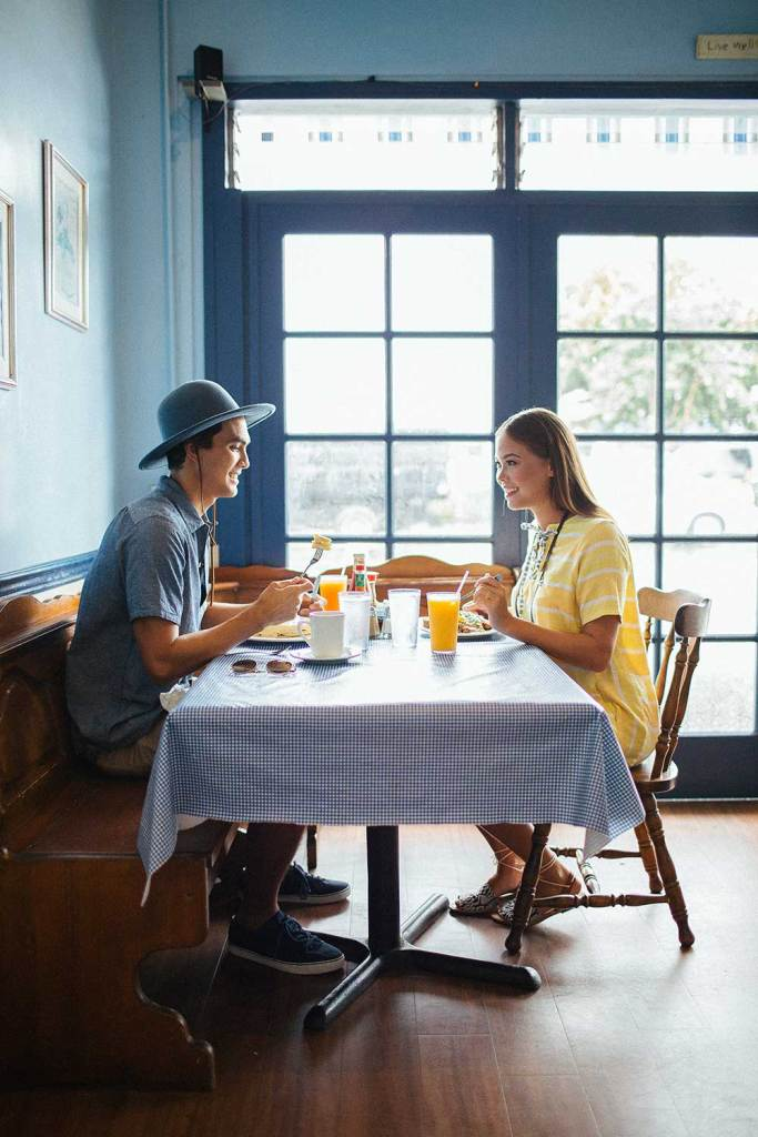 man in hat and woman in yellow dress sitting at breakfast table