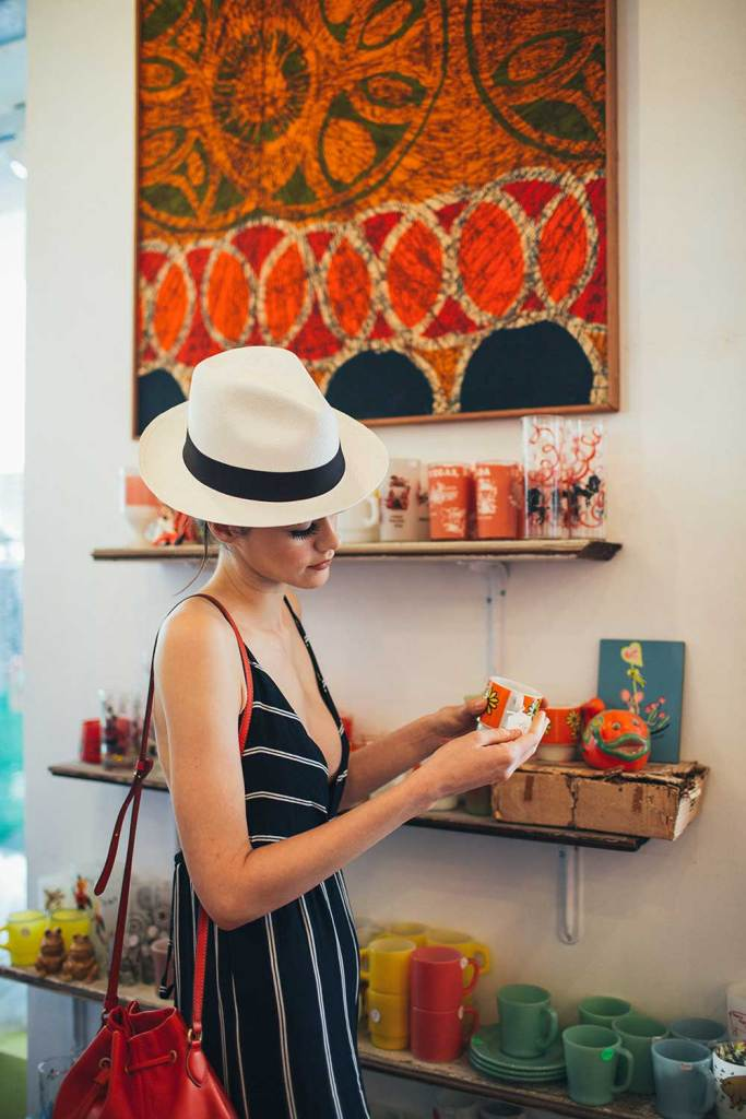 woman in hat and black stripe dress holding a cup inside a boutique