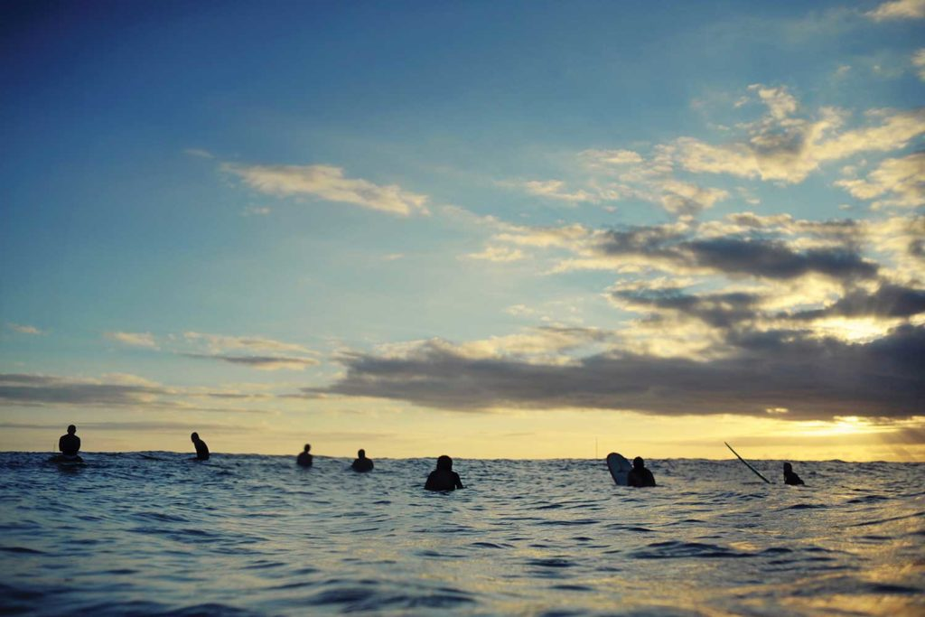 surfers in the ocean at sunset
