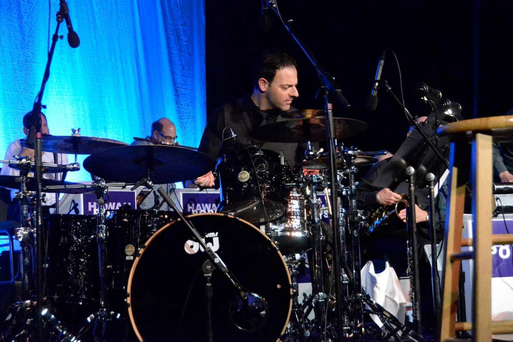 man in black shirt playing a drum set