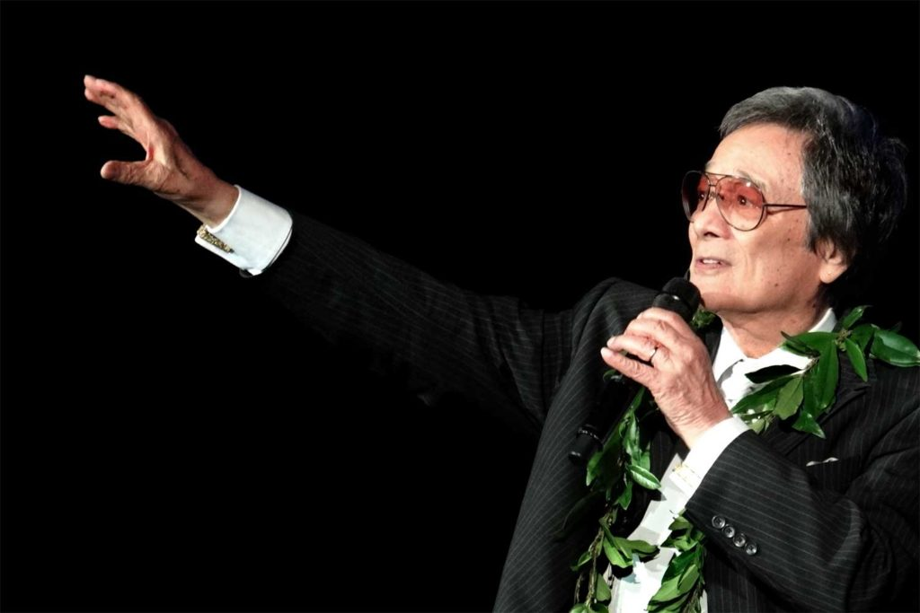 man in black suit wearing lei holding microphone singing