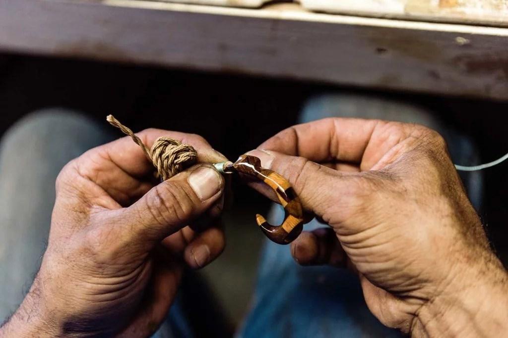 Leleo's hands making inlay wood Hawaiian hook jewelry