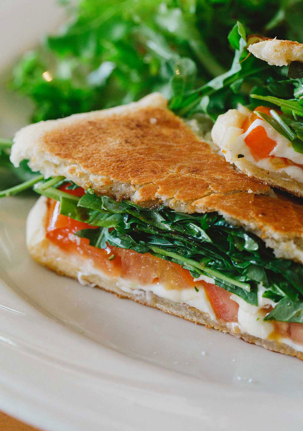 White plate with half triangle sandwich and greens