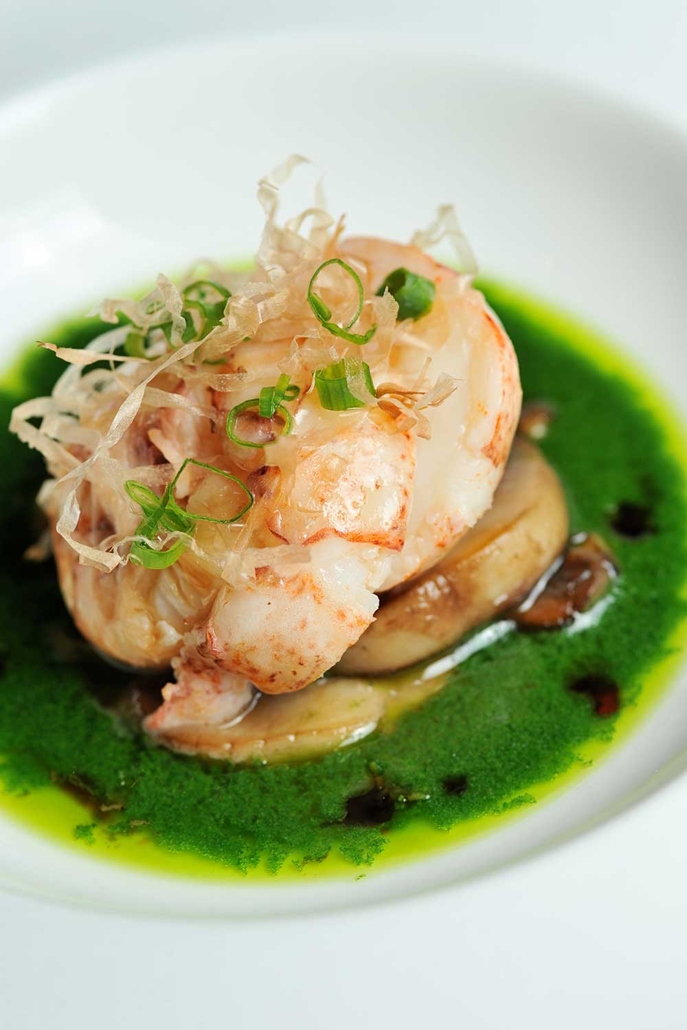 Shrimp dish placed nicely on some green colored sauce in white plate