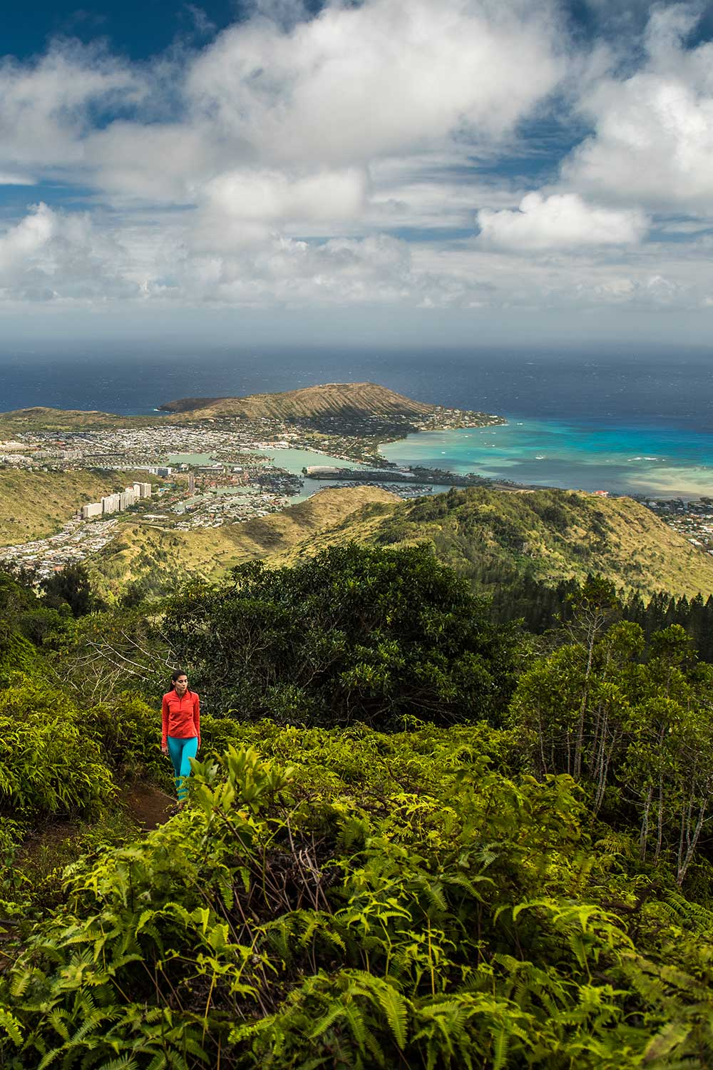View looking down from Kuli'ou'ou Ridge Trail with woman hiker wearing pink and blue in foreground