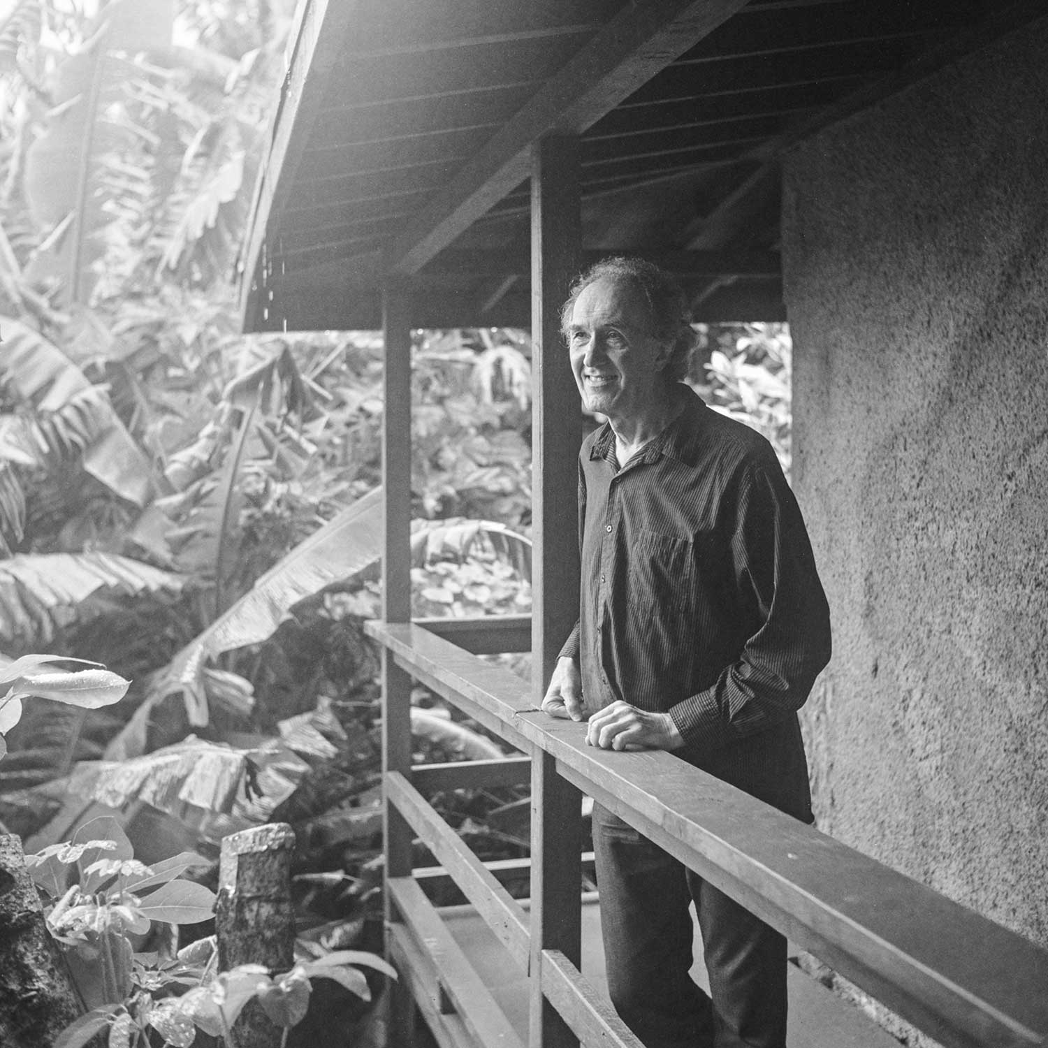 black and white photo of Pierre Grill standing on porch near forest