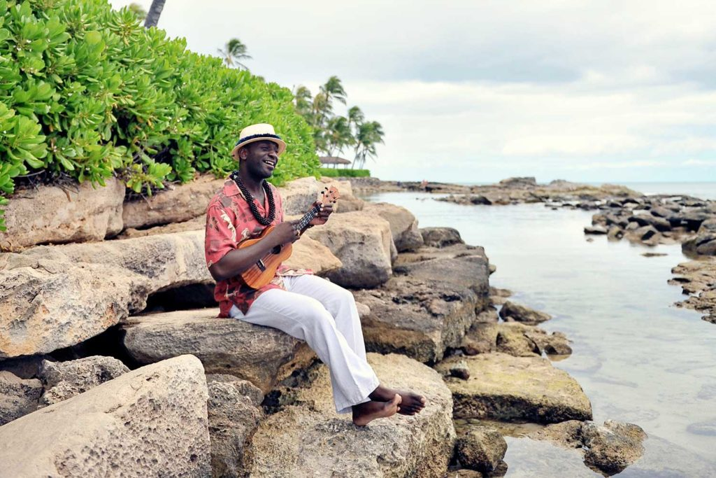 Ryan Kamakakehau Fernandez sitting on rocks playing ukulele