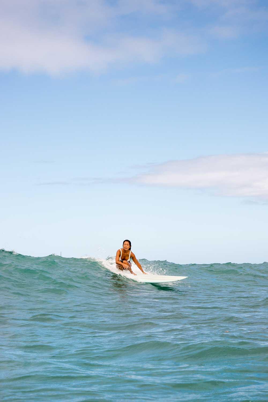 Nicolette Kim on surfboard in the ocean