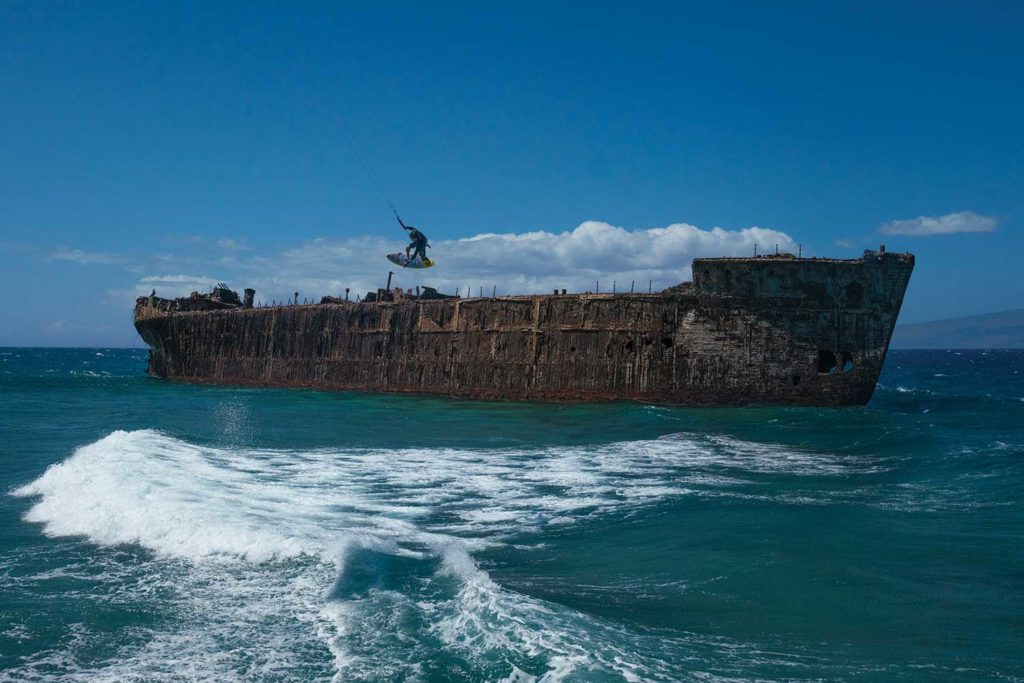 Kai Lenny kite surfing in front of abandoned rusted freighter in ocean