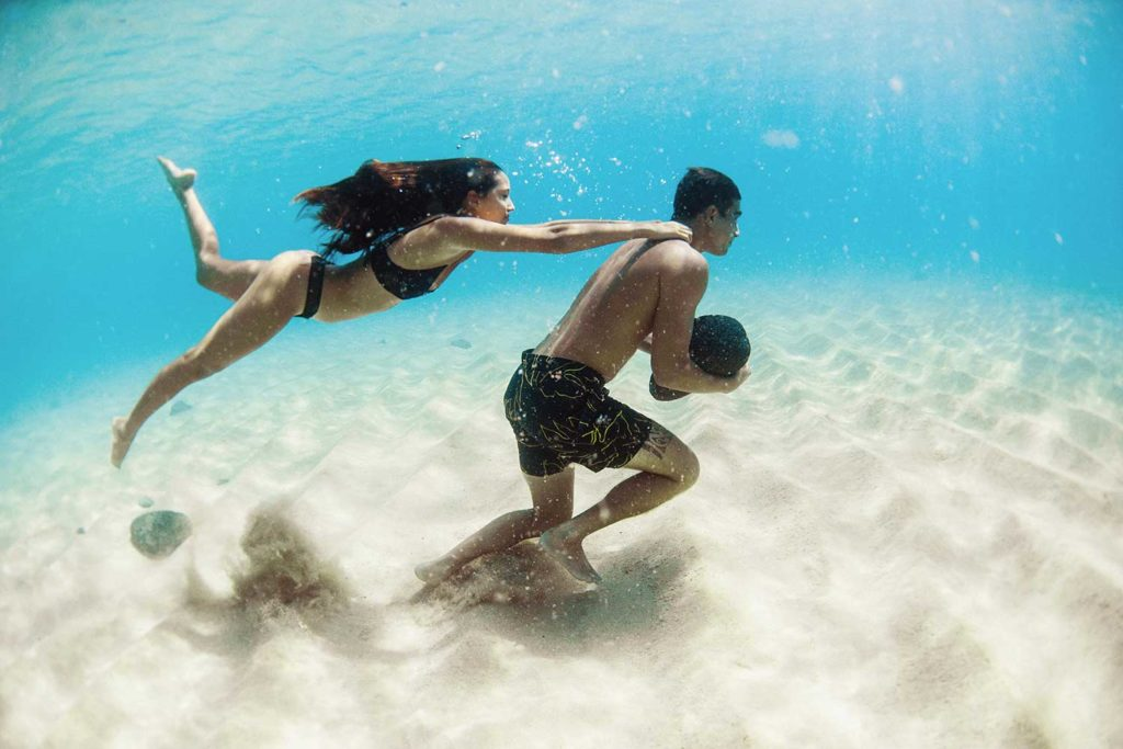 woman holding man walking underwater with rock