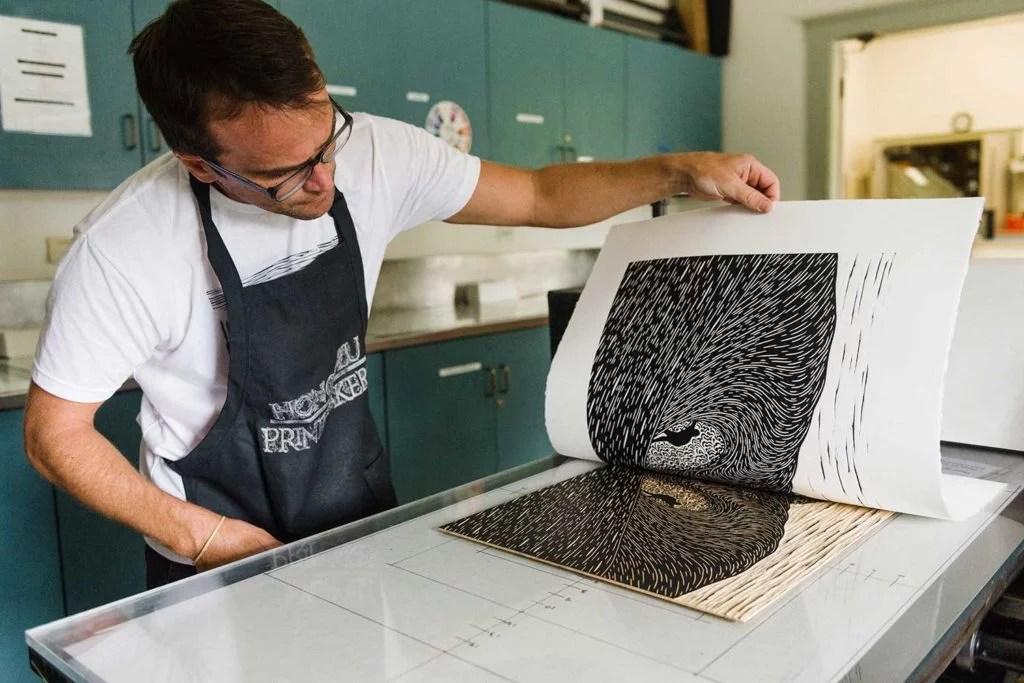 Steven Kean pulling paper away from a woodblock print