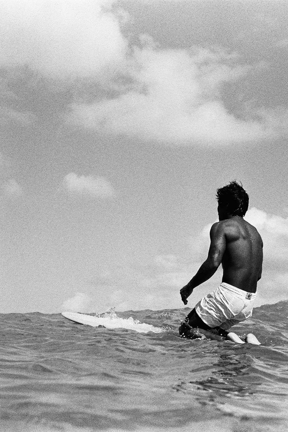 black and white photo of Toots kneeling on surfboard in ocean
