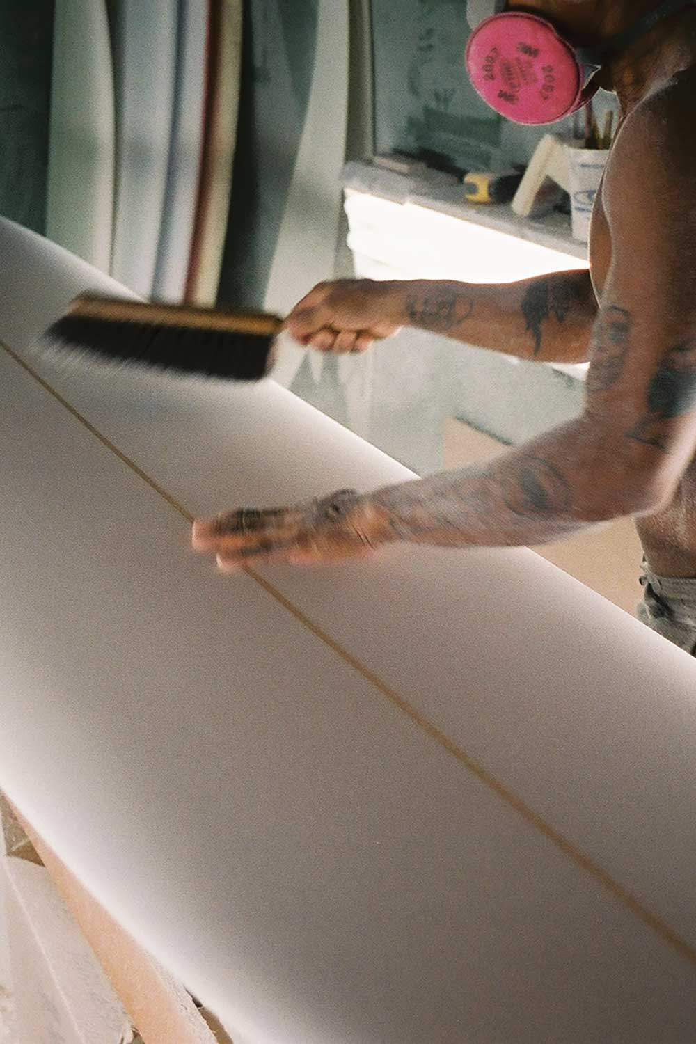 Toots brushing sawdust from surfboard