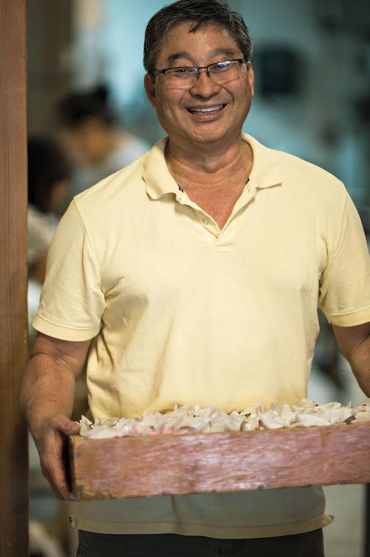 Nisshodo Mochi worker holding a tray of mochi.