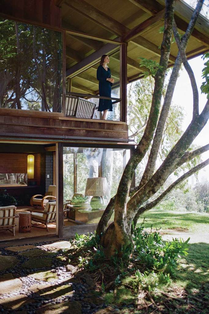 Woman on the second deck of the Liljestrand House with tree in foreground