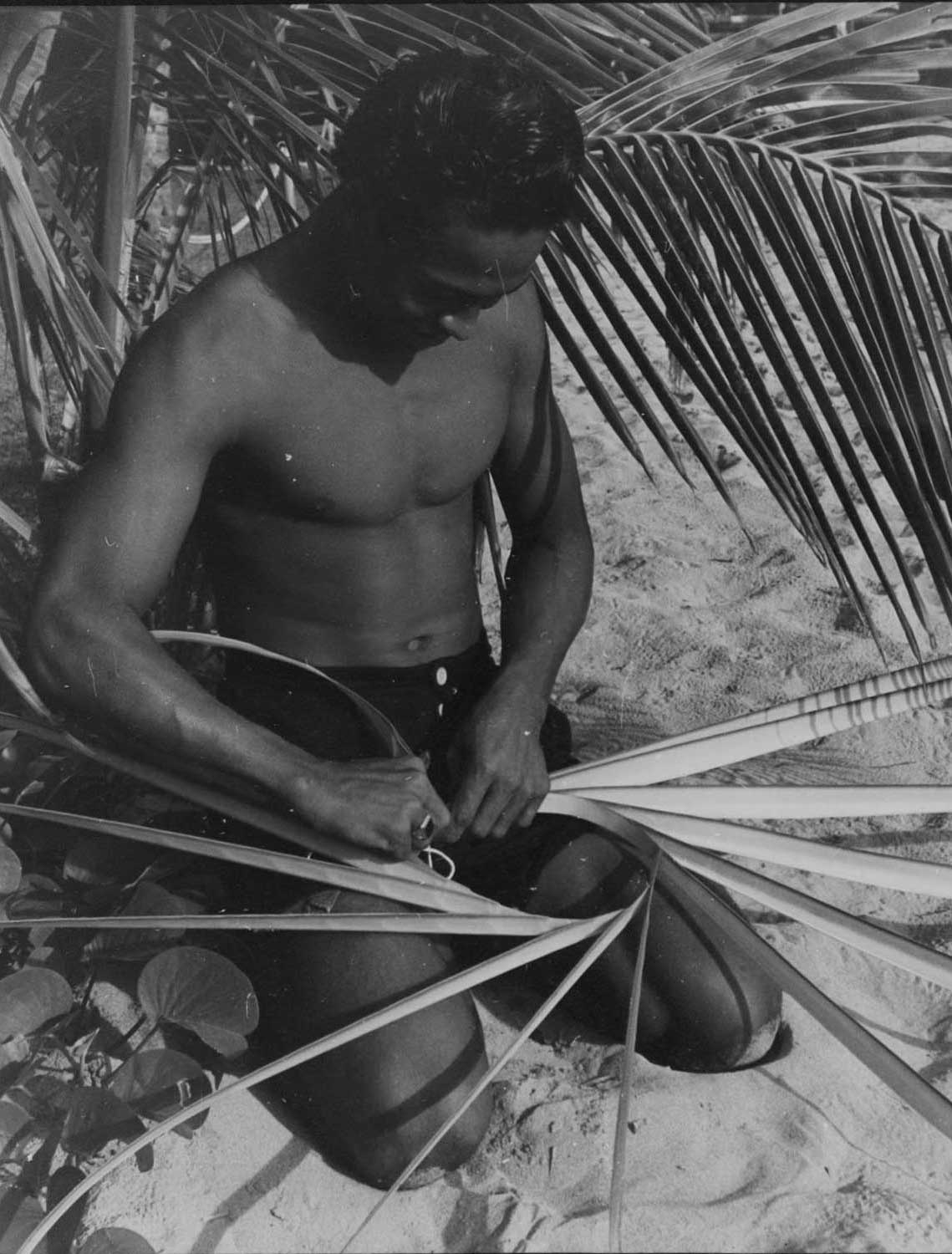 Black and white developed image of a man weaving with coconut leaves.