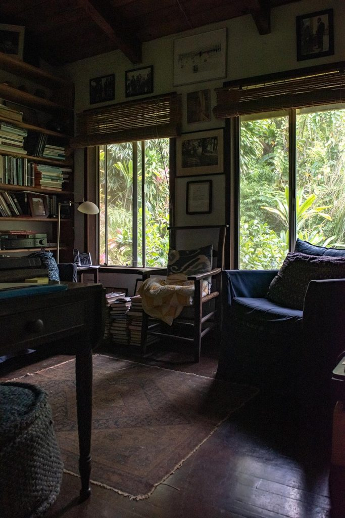 A living room with two chairs, two windows, and a book shelf full of books.