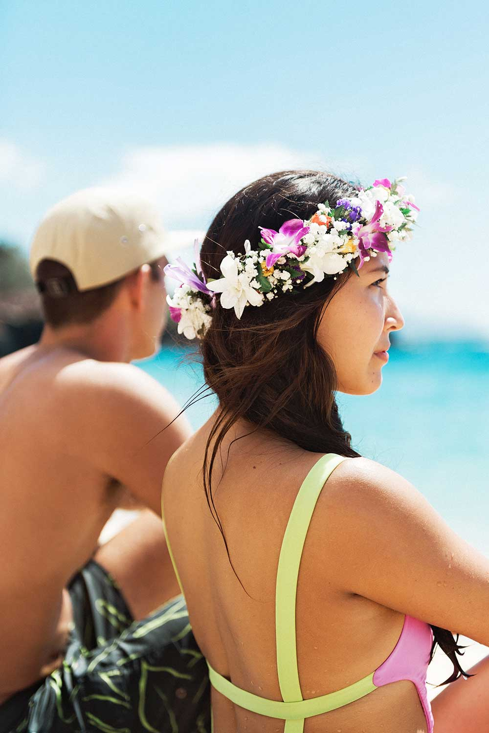 Woman with lei in hair and man sitting near ocean