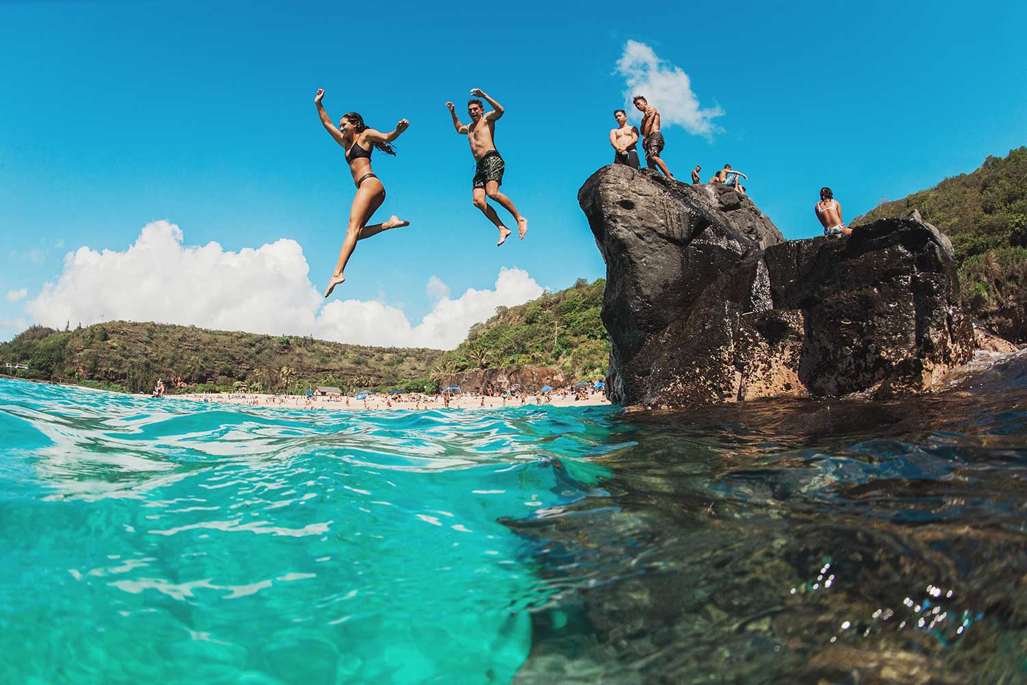 people jumping from rocks into ocean