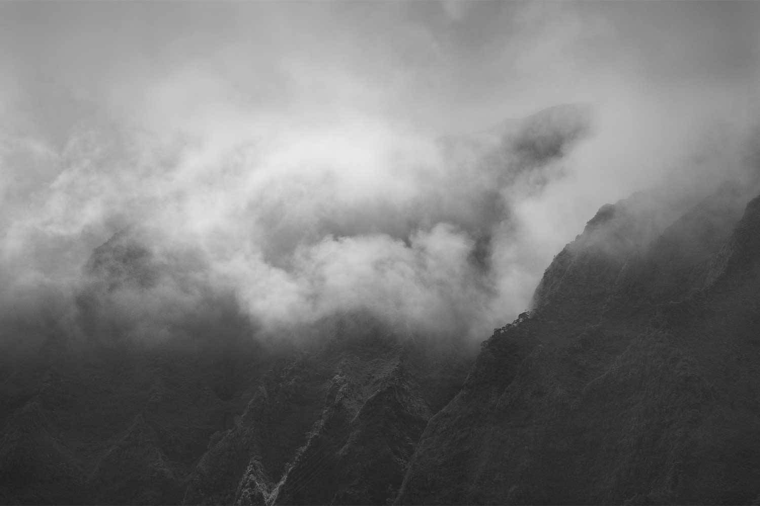 Black and white image of clouds covering the peaks of the Koolau mountain range