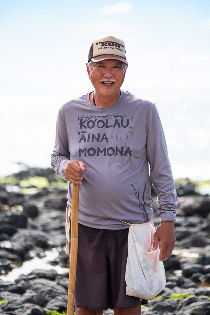Older man standing near the ocean and smiling