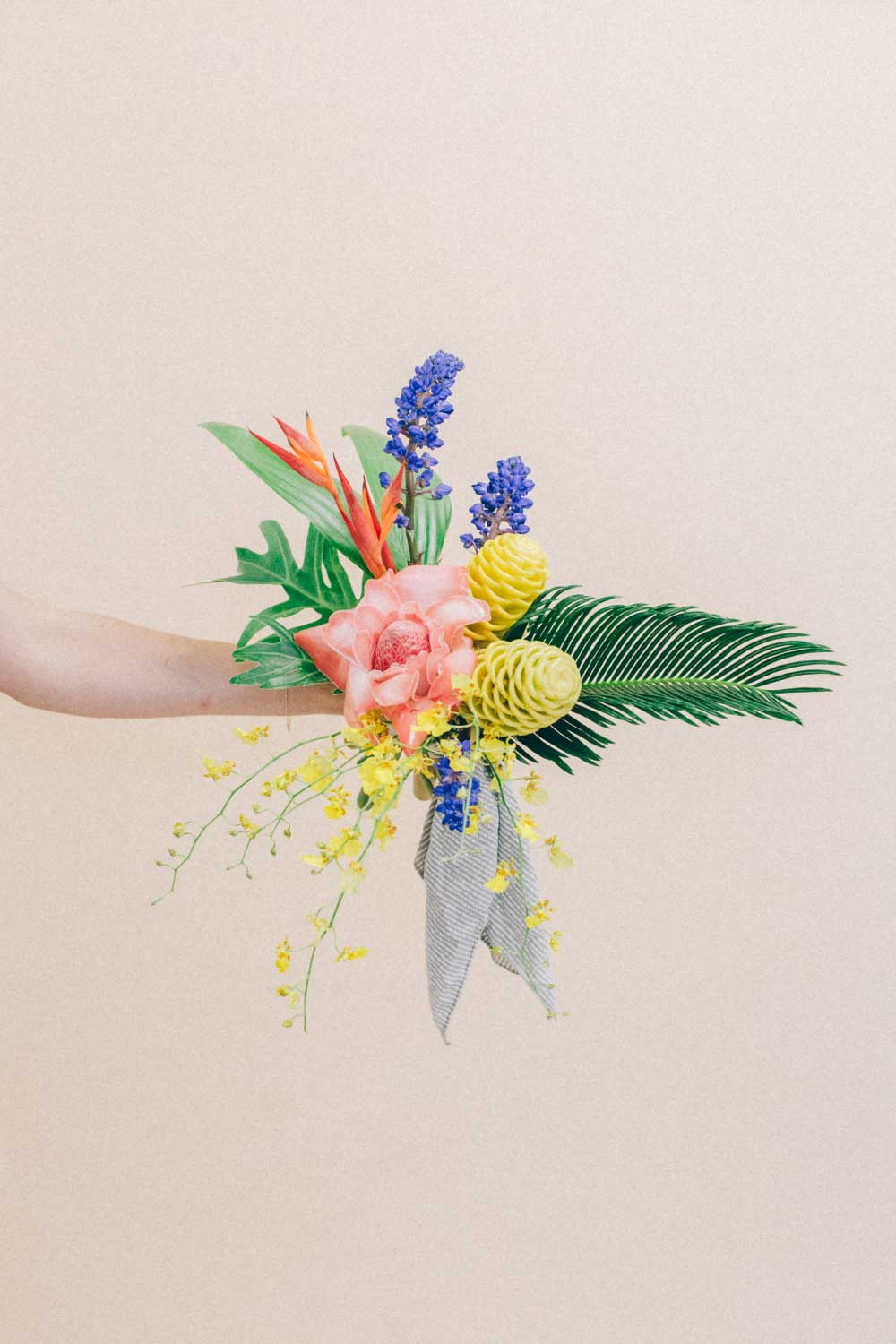 A hand holding a colorful flower bouquet