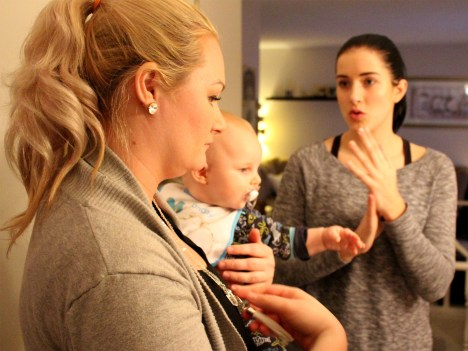 Miranda Veide holds son Xavier while talking with customers during a home show for her product line, To the Moon and Back on February 23rd, 2017.