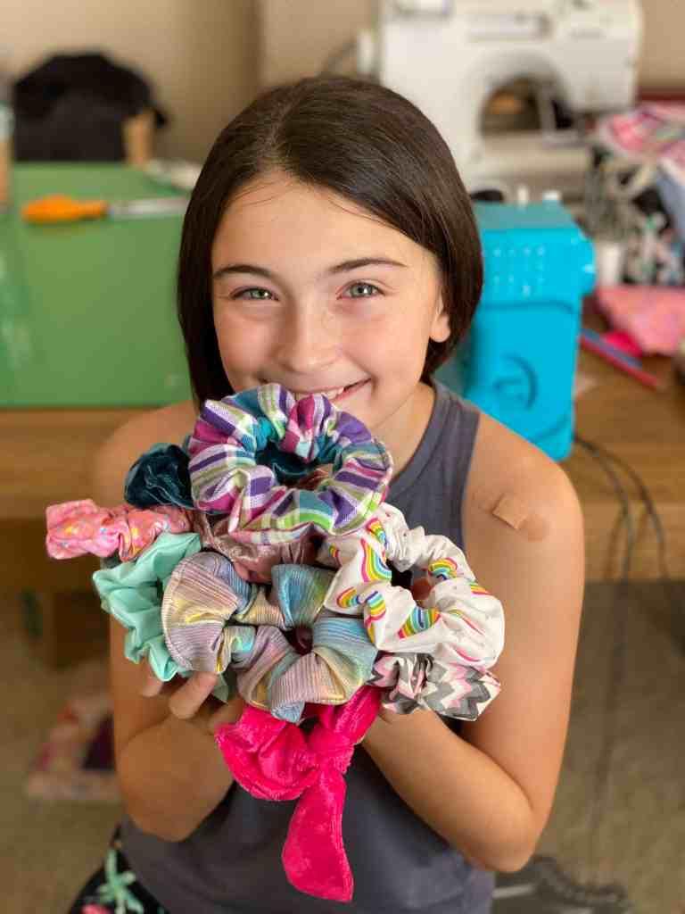 girl holding scrunchies