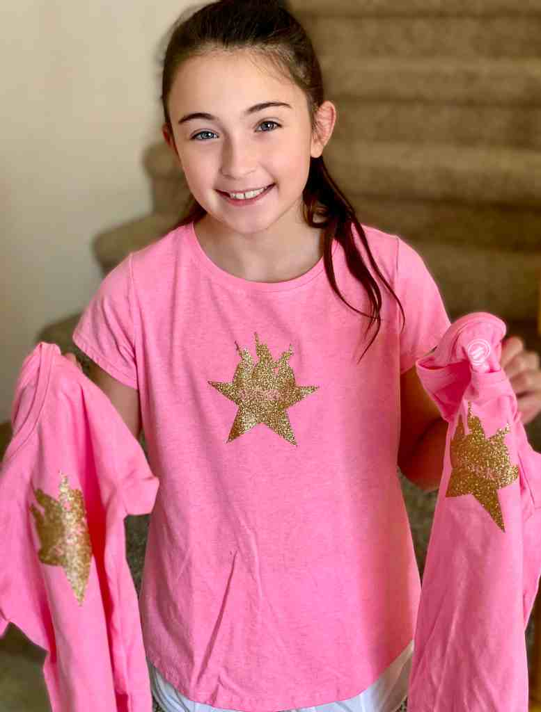girl in pink shirt with gold star