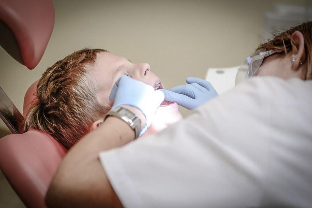 Boy getting his teeth examined by a dentist
