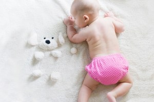 baby with pink diaper on blanket