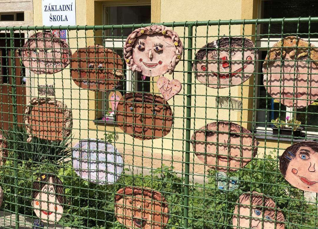students' clay faces hanging on a school's fence
