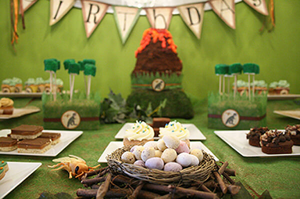 Dinosaur Party. Greenery Inspired Parties | Halfpint Design - This green backdrop is awesome for a dinosaur party. I love the volcano cake, moss cake pops, and dino eggs.